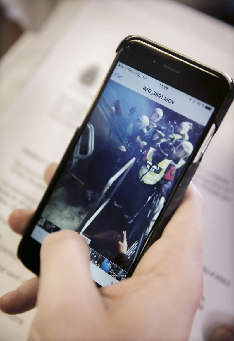 På knä. Martin Lundgren visar upp ett klipp där polismannen slår honom i huvudet två gånger med en batong. Martin, klädd i svart jacka, försöker skydda sig med händerna.